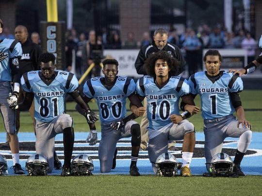 Lansing Catholic players kneel